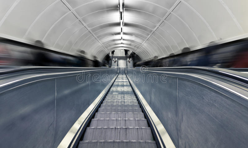 Blurred people on escalator at rush hour. Blurred people on escalator. London subway station at rush hour royalty free stock photo