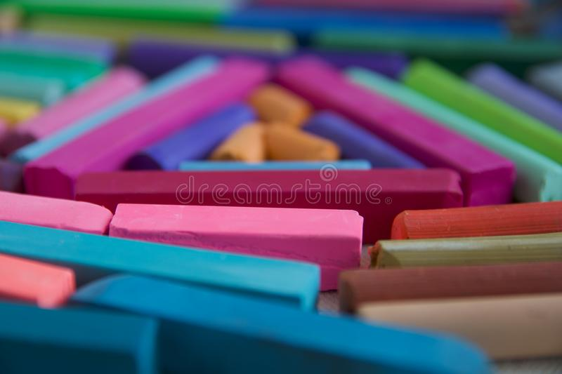 Blurred photo with chopsticks of multicolored art pastels suitable for the background. Symbol of creativity, joy, rich choice royalty free stock photo