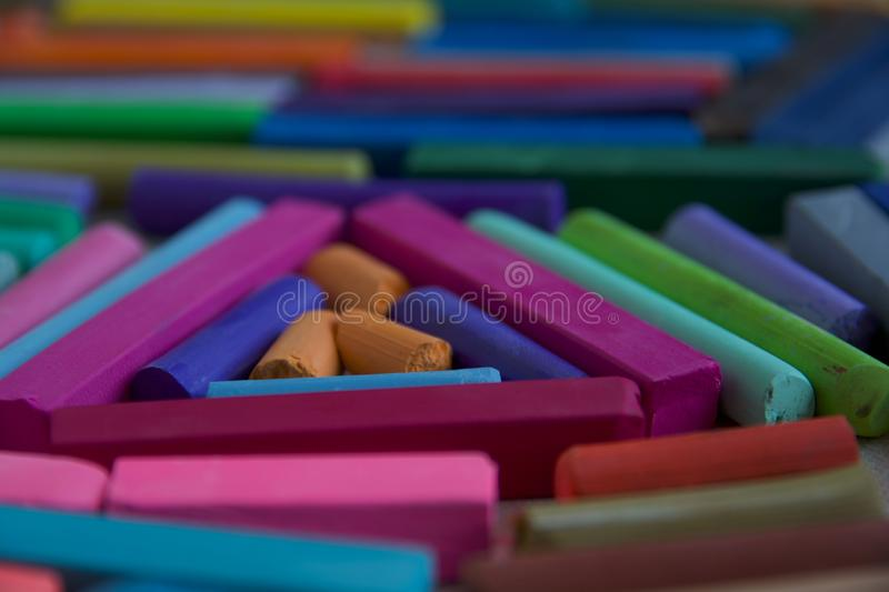 Blurred photo with chopsticks of multicolored art pastels suitable for the background. Symbol of creativity, joy, rich choice royalty free stock images