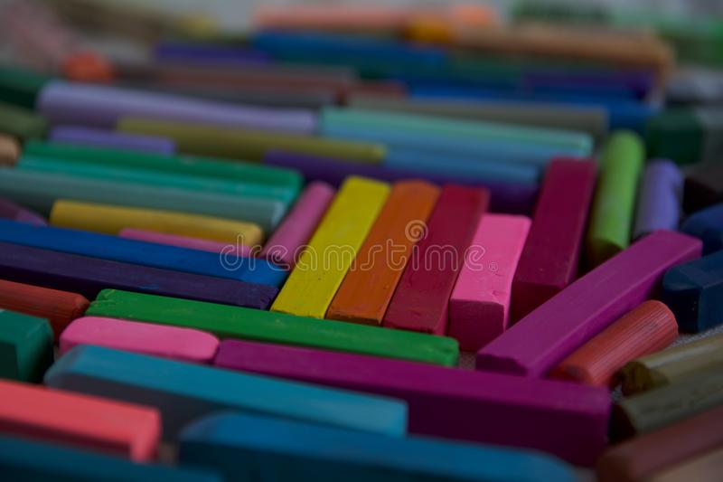 Blurred photo with chopsticks of multicolored art pastels suitable for the background. Symbol of creativity, joy, rich choice stock photo