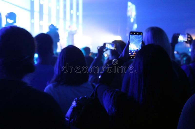 Blurred photo people at a concert stand and shoot on the phone stock image
