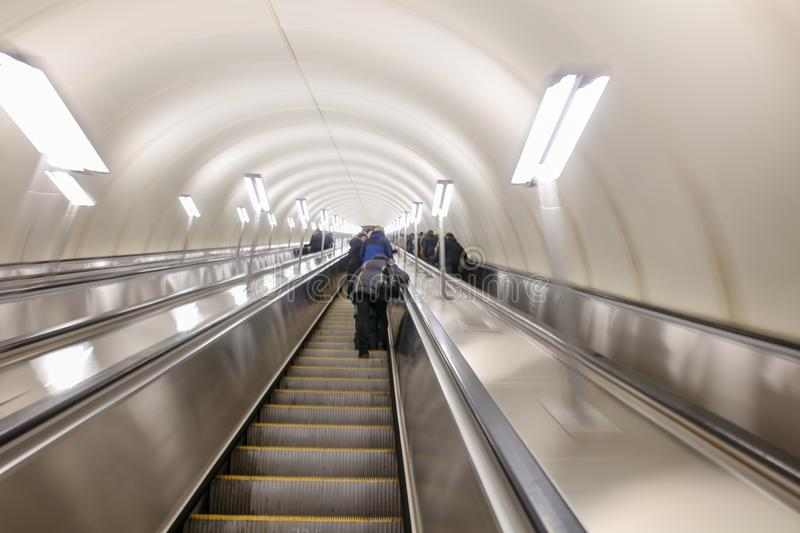 Blurred photo of people on the escalator in the subway.  stock image