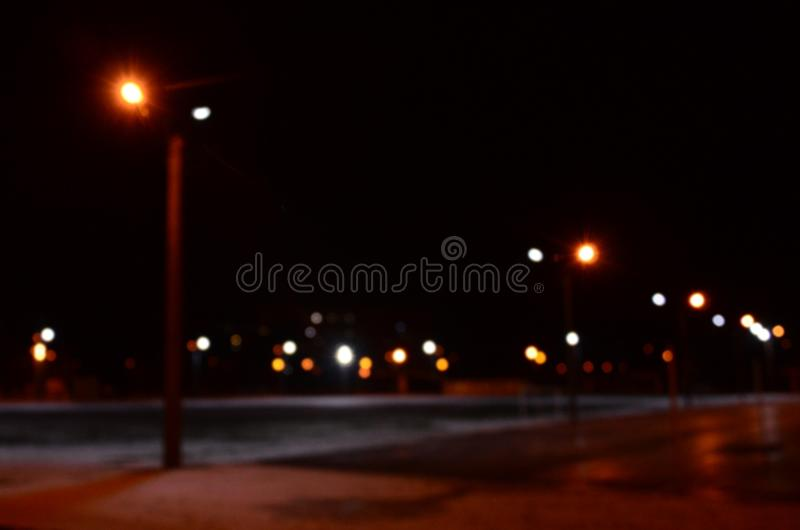 Blurred photo of school playground at night with bright lights stock photography