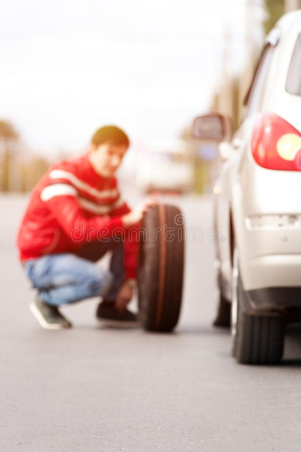 Male driver after car breakdown on cityroad. Blurred picture of young man sitting near broken car and changing tyre wheel. Male driver agter car breakdown on stock images