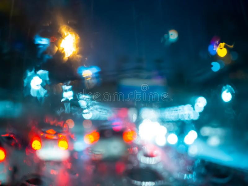 Blurred rain drops on car window with road light bokeh on rainy season abstract background. Water drop texture on the glass from the rain in car driving stock image