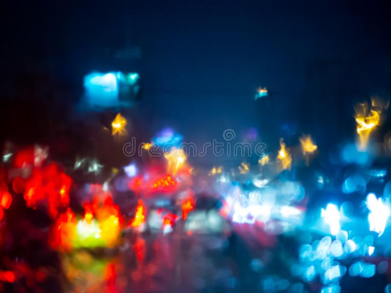Blurred rain drops on car window with road light bokeh on rainy season abstract background. Water drop texture on the glass from the rain in car driving royalty free stock image