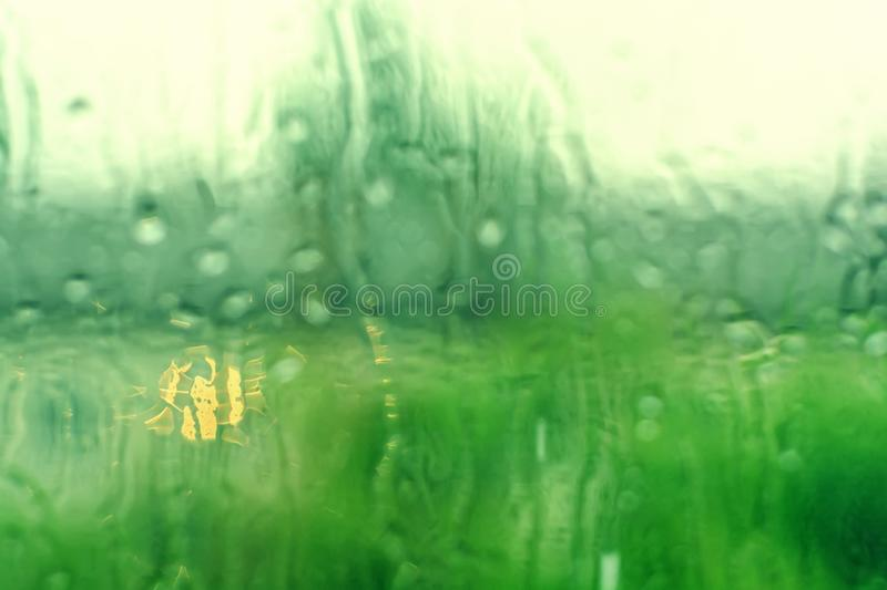 Blurred rain drops on a window background. Nature green bokeh royalty free stock photography