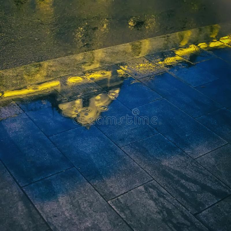 Blurred reflection of a beautiful building in a puddle on the asphalt. Rainy night in the urban street. Abstract bright stock images
