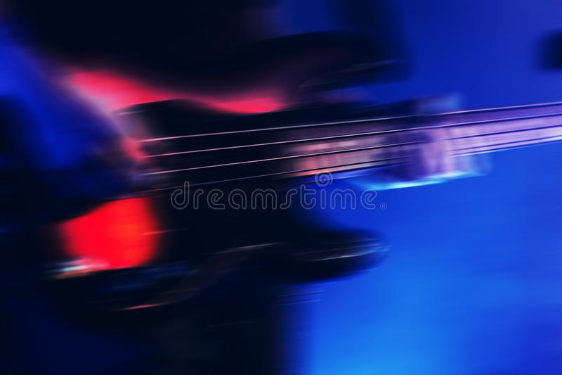 Blurred rock music background, bass guitar. Player on a stage with blue illumination royalty free stock photos