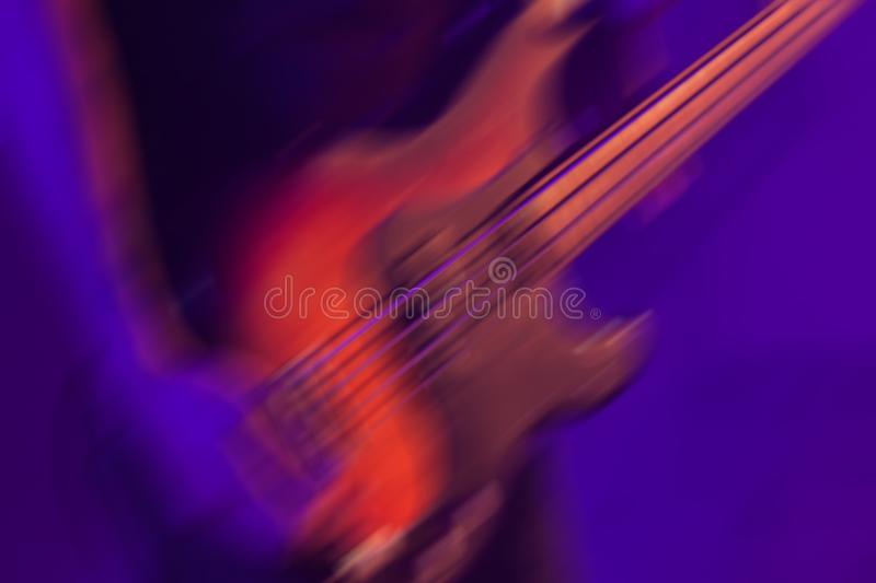Blurred rock music background, bass guitar. Player on a stage with blue and purple colorful illumination royalty free stock photos