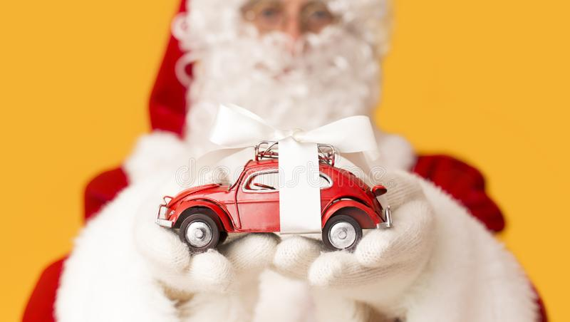 Blurred Santa Claus suggesting toy car with present bow. Christmas promo. Blurred Santa Claus suggesting toy car with present bow on orange background stock photography