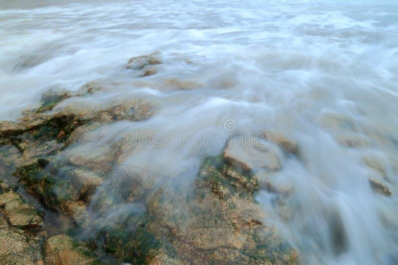 Blurred sea waves over rock. On a shingle beach on the Jurassic Coast in Devon stock image