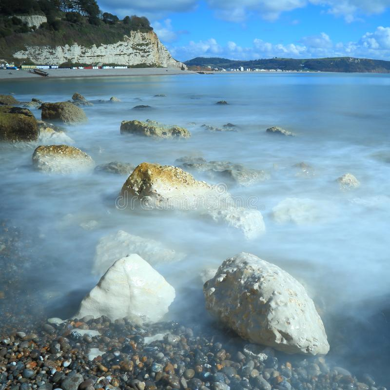 Blurred sea waves on the shingle beach. Near village of Beer in Devon on the Jurassic Coast natural World Heritage Site royalty free stock images