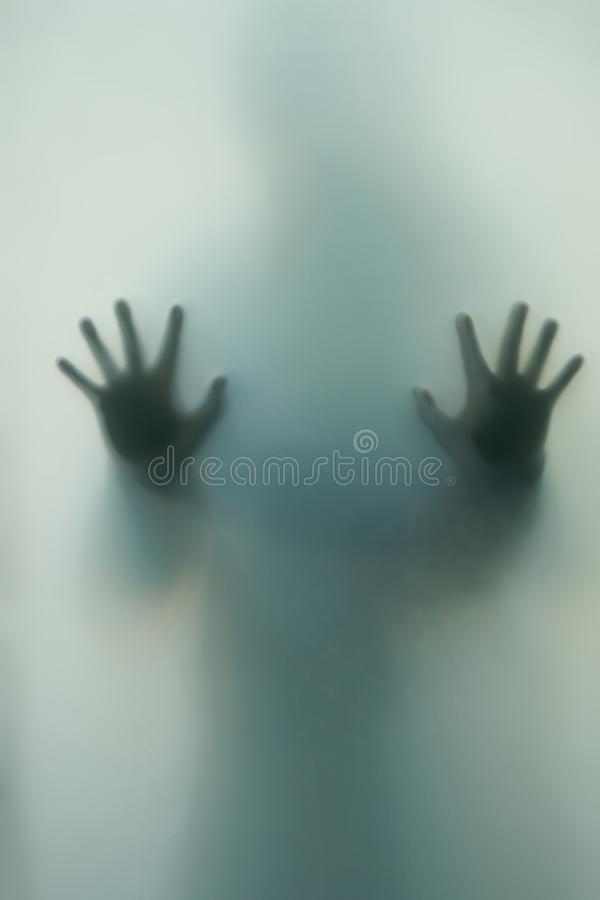 Blurred shadow of a horror woman. The hands on the glass. Dangerous person behind frosted glass. Person of mystery Halloween royalty free stock image