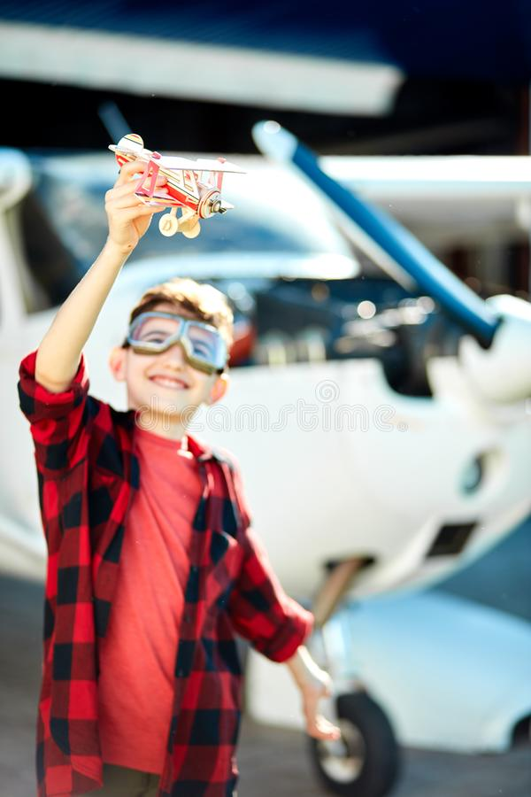 Blurred shot of a boy playing with toy plane near single-engine aircraft royalty free stock photo
