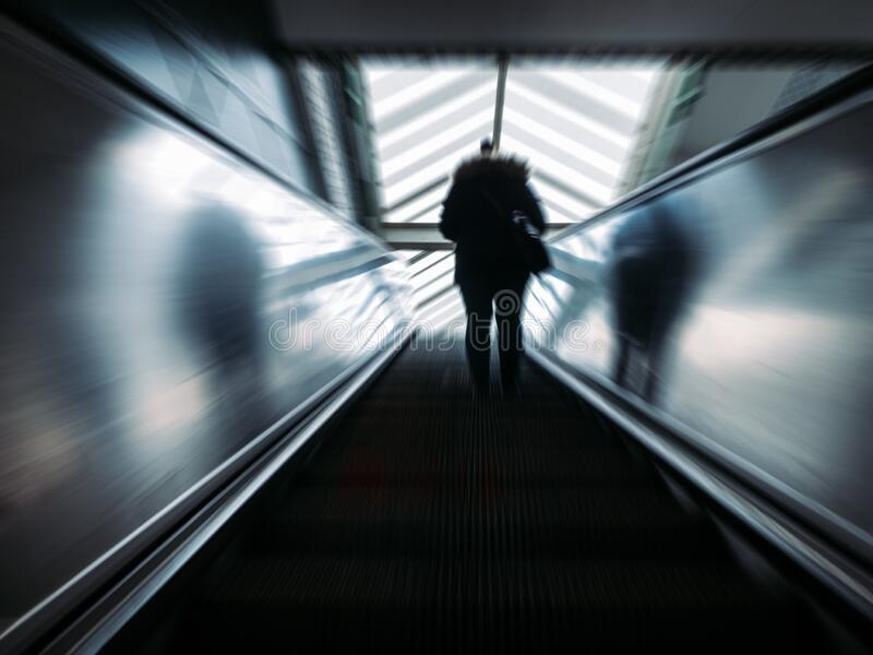 Blurred shot of a man wearing business attire, riding in the escalator. A blurred shot of a man wearing business attire, riding in the escalator stock photography
