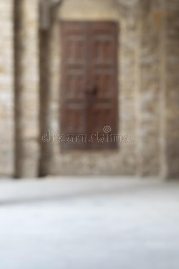Blurred shot of old abandoned stone bricks wall with grunge weathered wooden door stock images