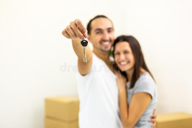 Blurred shot of young family extremely happy because they bought a new house. Man showing keys to the camera. stock photography