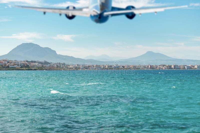 Blurred silhouette of airplane flying over the sea and beach. Travel concept stock image