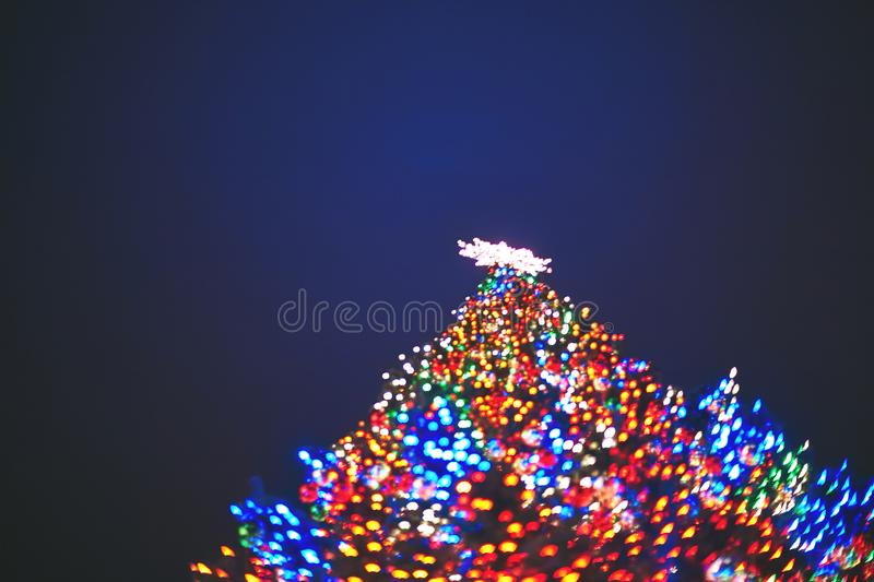 Blurred silhouette of a Christmas tree decorated with a star and garlands of red, green and blue on the background of the night royalty free stock images