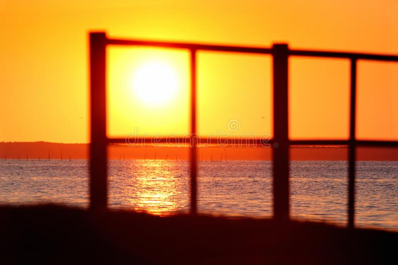 Blurred silhouette of a fence on a seashore during the sunset.  royalty free stock photography