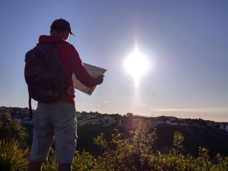 Blurred silhouette of a tourist guy with a map, on the background of the city on a hill, at sunrise stock image