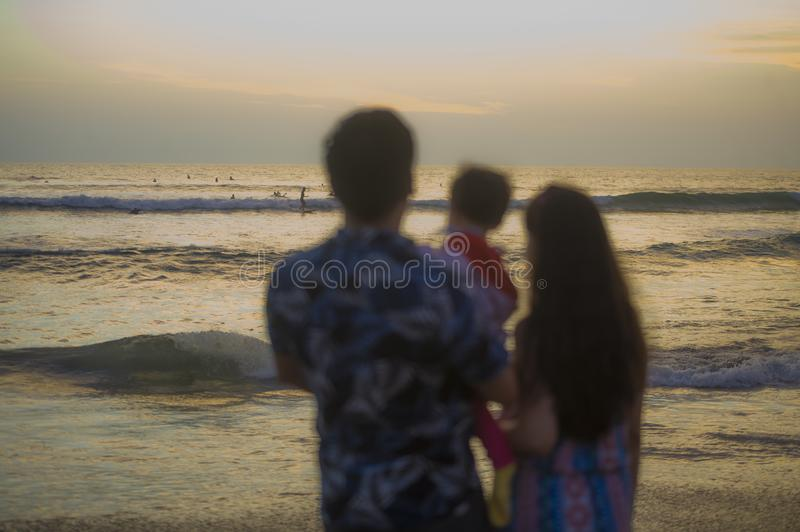 Blurred silhouette of young happy and beautiful Asian Chinese couple holding baby girl daughter enjoying sunset beach together stock photos
