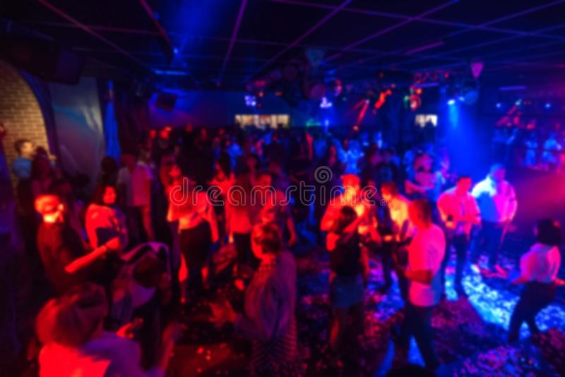 Blurred silhouettes of a group of people dancing in a nightclub on the dance floor under colorful spotlights royalty free stock images