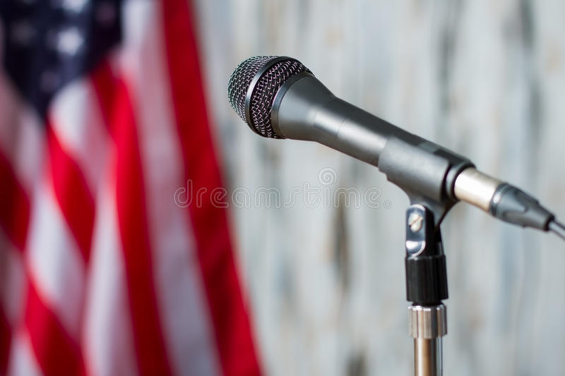 Blurred US flag and microphone. Microphone on stand beside banner. Entire nation will be watching. Tribune waiting for the speaker royalty free stock photo