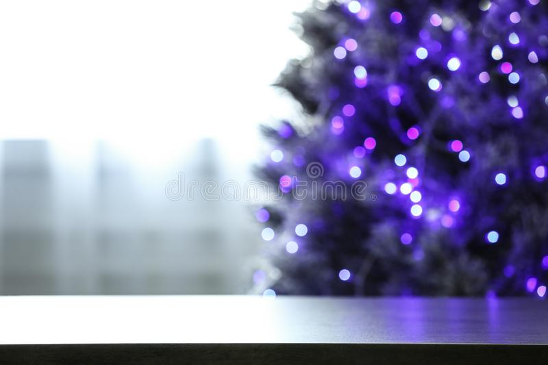 Blurred view of beautiful Christmas tree with purple lights near window indoors, focus on table. Space for text royalty free stock photo