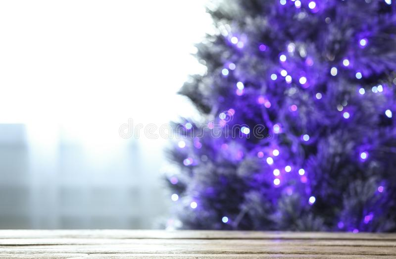 Blurred view of beautiful Christmas tree with purple lights near window indoors, focus on wooden table. Space for text royalty free stock photo