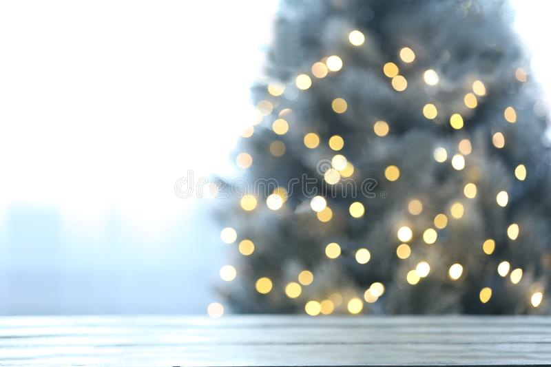 Blurred view of beautiful Christmas tree with yellow lights near window indoors, focus on wooden table. Space for text royalty free stock photography
