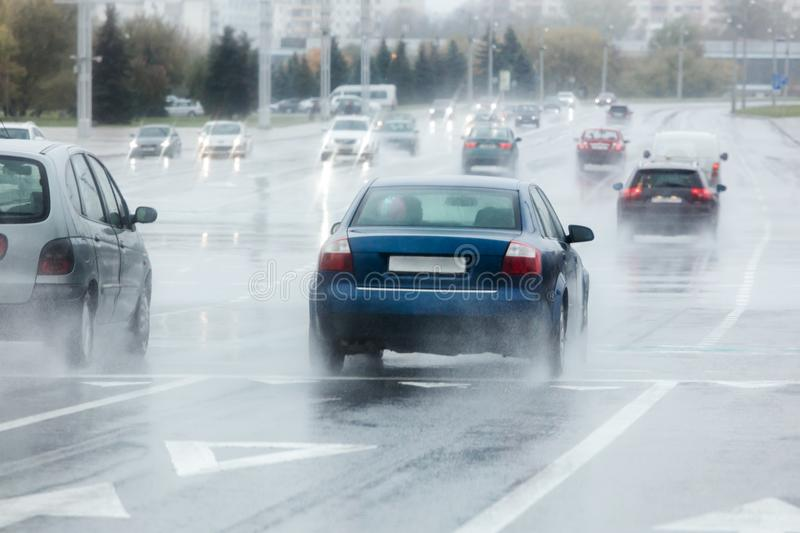 Blurred view of city cars moving along wet road during rainy day. Blurred view of city cars moving along wet road during heavy rain stock photography