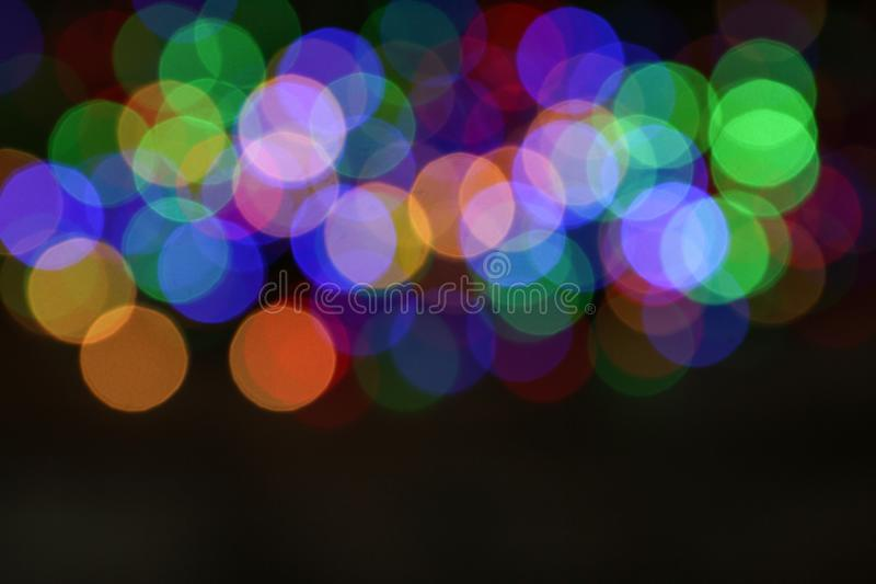 Blurred view of colorful Christmas lights. On dark background royalty free stock image