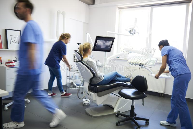 Blurred view of dentists and woman in dentist`s clinic royalty free stock image