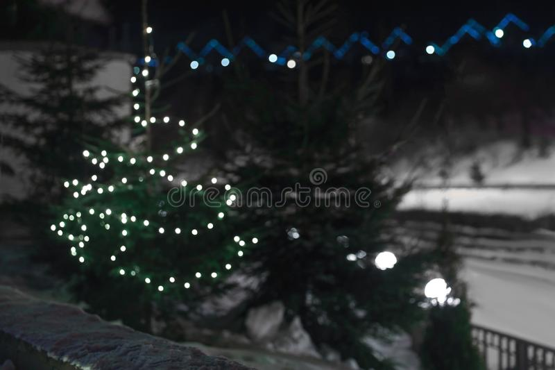 Blurred view of fir tree with Christmas lights and snow. Outdoors royalty free stock images