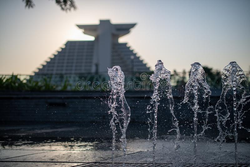 Blurred view of a landmark hotel with water fountains in the foreground royalty free stock photo