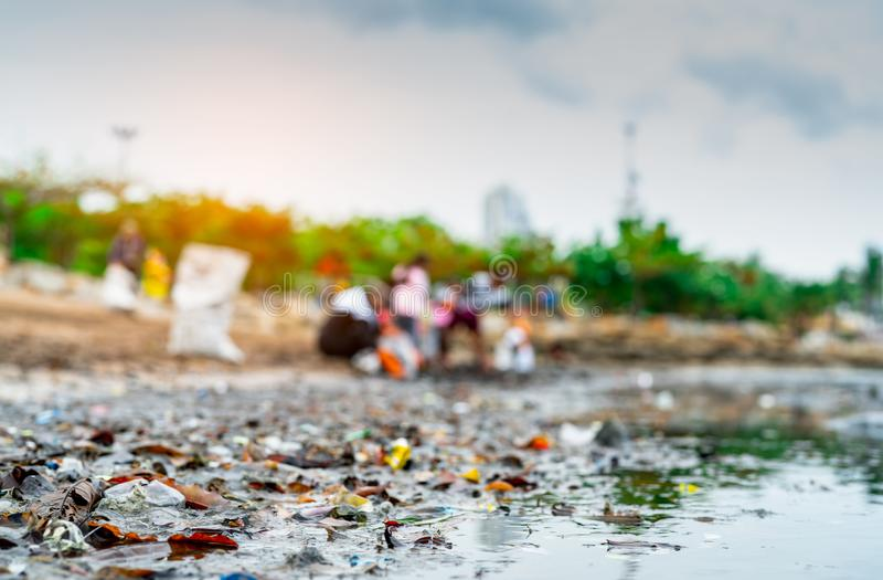 Blurred of volunteers collecting garbage. Beach environment pollution. Volunteers cleaning the beach. Tidying up rubbish on beach. Oil stains on the beach. Oil royalty free stock image