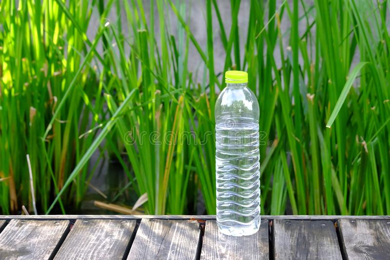 Close up a bottle of drinking water on the old wooden ground floor with stock images