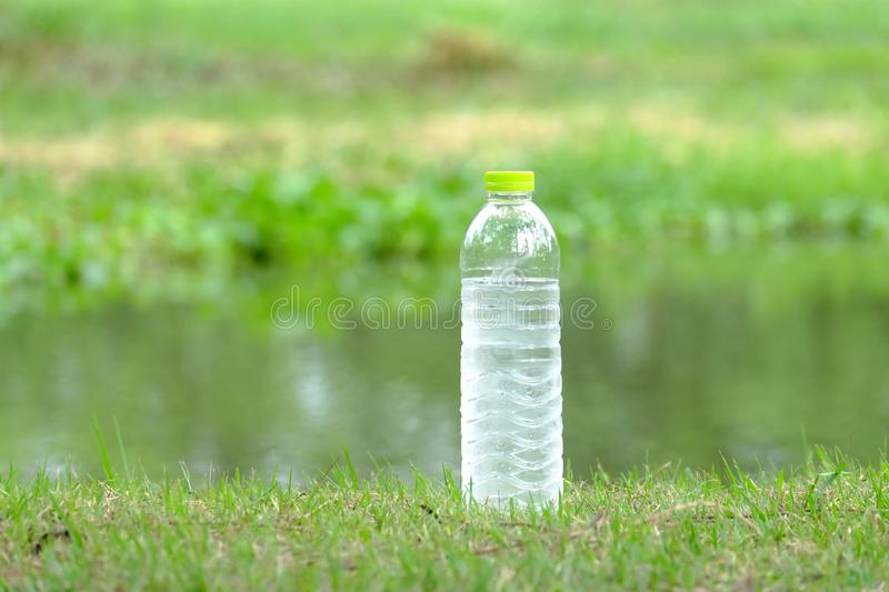 A bottle of cold drinking water on the grass ground at the park with royalty free stock images