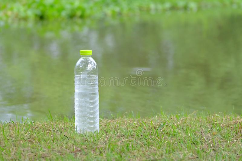 A bottle of cold drinking water on the grass ground at the park with stock images