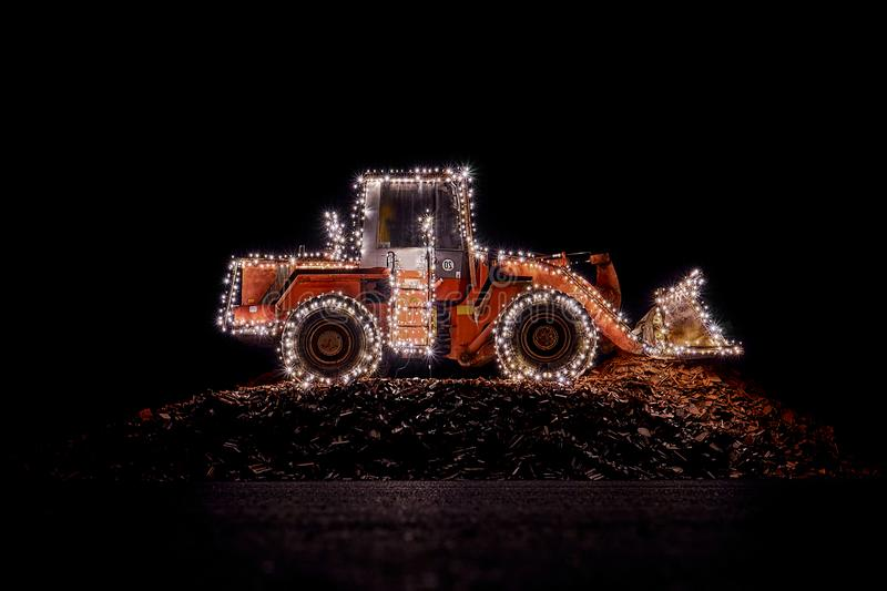 Blurred wheel loader decorated with lights at christmas royalty free stock photo