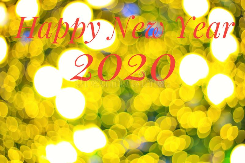 Blurred yellow bokeh lights as background, with red color text Happy New Year 2020. Holidays concept royalty free stock images