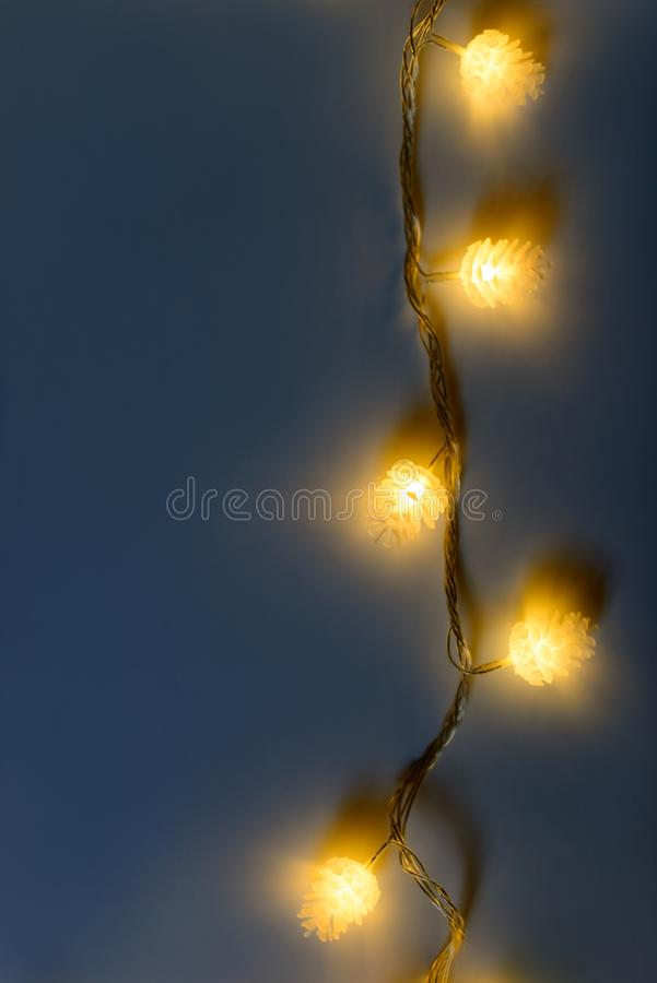 Blurred yellow christmas lights in shape of cones on dark background, low depth of focus. stock images