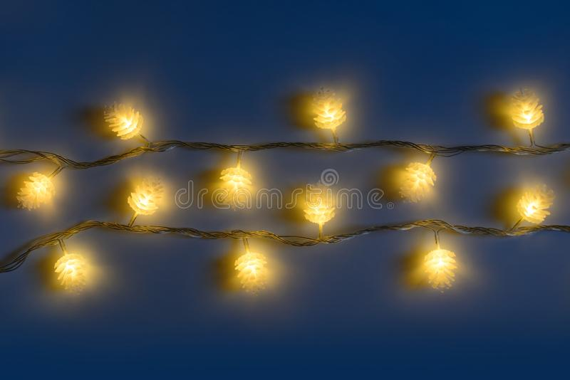 Blurred yellow christmas lights in shape of cones in three rows on dark background , low depth of focus. stock photography