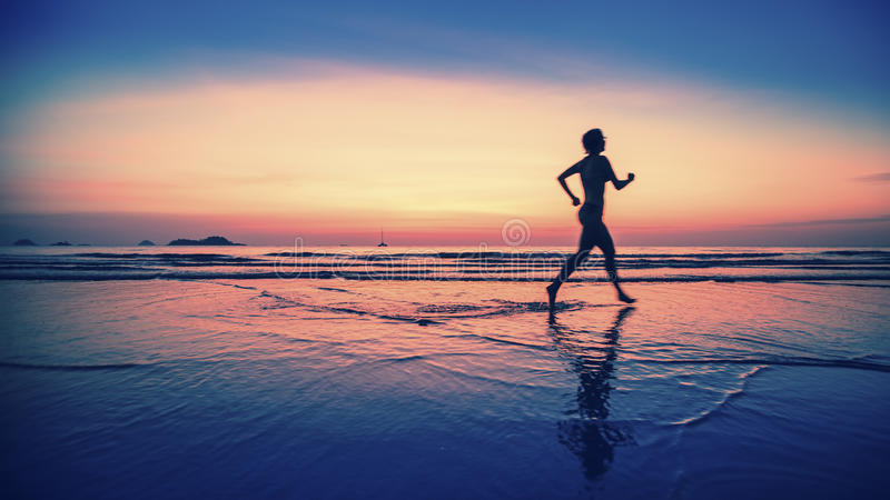 Blurring silhouette of running woman during the bright sunset. Blurring silhouette of running woman on the beach during the bright sunset royalty free stock photo