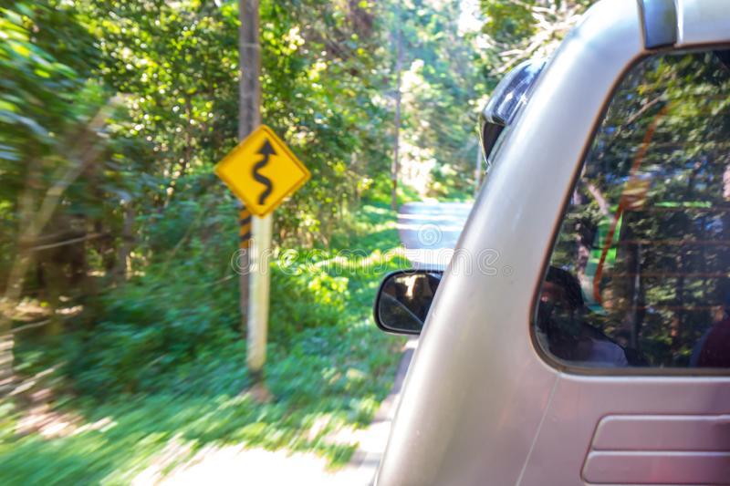 Blurry abstract image photo of fast car with warn curve sign warning for danger. royalty free stock photos