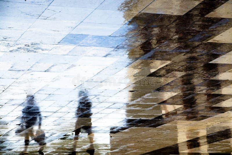 Blurry abstrakte Schattensilhouette Reflexionen von zwei Menschen auf der Straße der Stadt lizenzfreie stockbilder