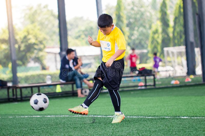 Blurry ball with Asian kid soccer player speed run to shoot ball to goal on artificial turf. Kid soccer player training or football match. Asian boy soccer royalty free stock photos