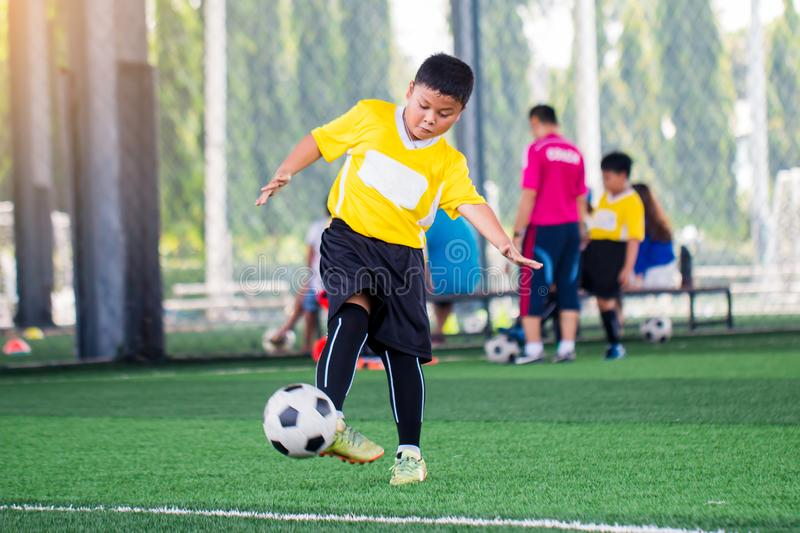 Blurry ball with Asian kid soccer player speed run to shoot ball to goal on artificial turf. Kid soccer player training or football match. Asian boy soccer royalty free stock photo